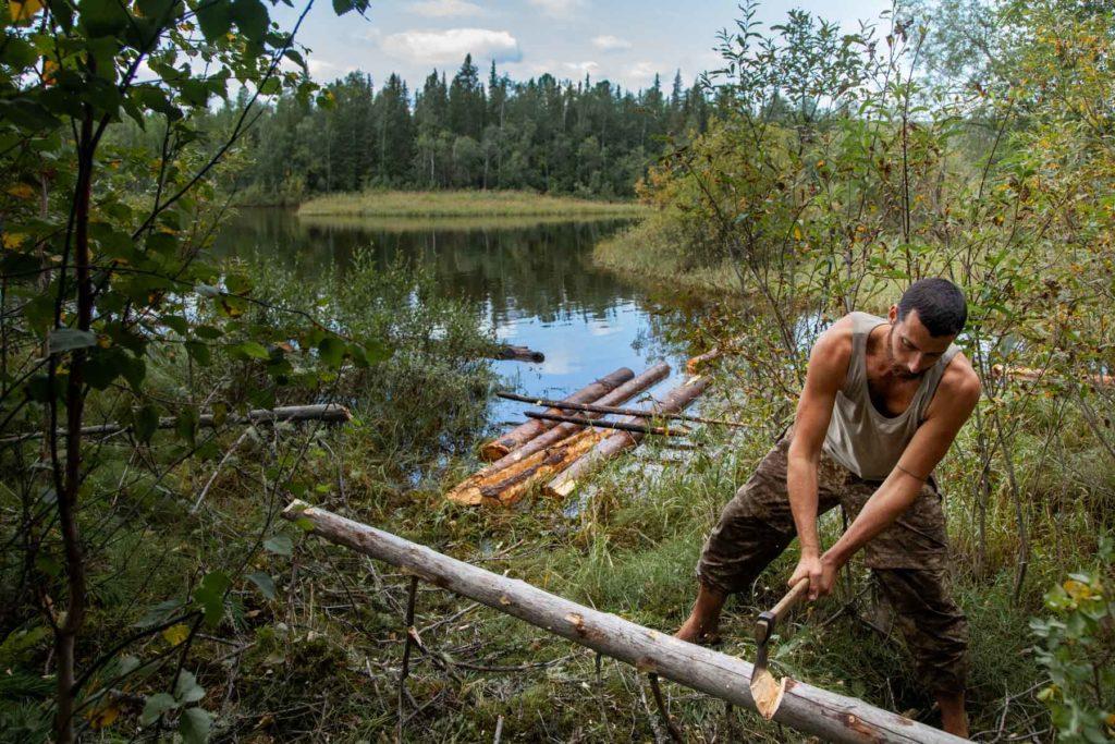 Baptiste Dulaar coupant un arbre, au bord de l'Oural
